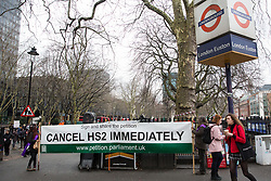 London, UK. 12th January, 2018. Activists stand holding an anti-HS2 banner outside Euston station. Local residents and environmental campaigners are protesting against the planned felling of mature London Plane, Red Oak, Common Whitebeam, Common Lime and Wild Service trees in Euston Square Gardens to make way for temporary sites for construction vehicles and a displaced taxi rank as part of preparations for the HS2 high-speed rail line.