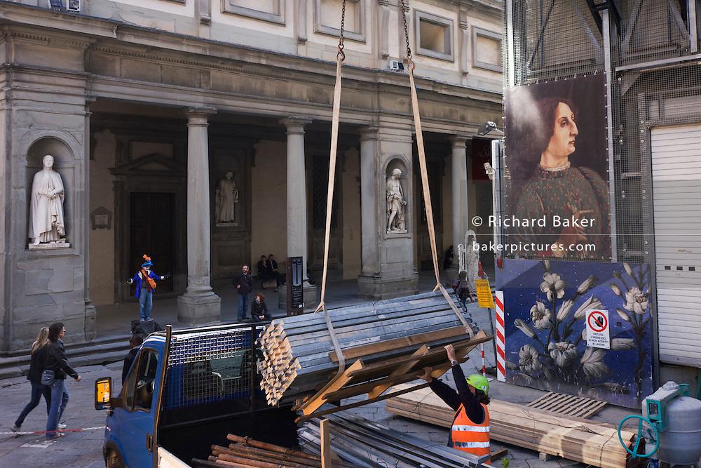 Construction workman and tourists beneath renaissance art  poster in Florence's Piazza degli Uffizi. .