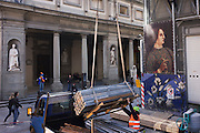 Construction workman and tourists beneath renaissance art  poster in Florence's Piazza degli Uffizi. .
