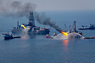 """June 10, 2010 , Vessels spray water on fllames caused by flare shooting off the  """"Discoverer Enterprise"""",  a barge set up after the Deepwater Horizon rig exploded and sank to the bottom of the Gulf of Mexico that is siphoning oil from the uncapped BP well.  The BP oil spill is the largest oil spill in American history."""