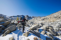 A woman wearing a backpack hiking in the snow through some high alpine landscape, Enchantment Lakes Wilderness Area, Washington Cascades, USA.