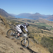 Callum Sprosen from Auckland in action during the New Zealand South Island Downhill Cup Mountain Bike series held on The Remarkables face with a stunning backdrop of the Wakatipu Basin. 150 riders took part in the two day event. Queenstown, Otago, New Zealand. 9th January 2012. Photo Tim Clayton