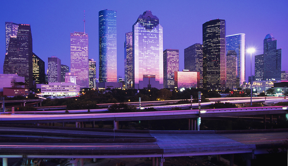 Houston, Texas skyline at night with purple light reflecting in skyscrapers with freeway in foreground.