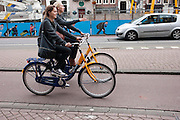 Twee vrouwen rijden op een OV-fiets over het Rokin in Amsterdam.<br /> <br /> Two women are riding on an OV-fiets, a rental bike, at the Rokin in Amsterdam.