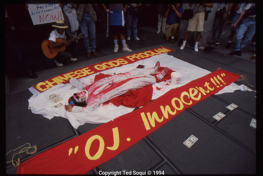 "The OJ Simpson trial and media circus.<br /> A bizarre performance artist doused in red paint and dancing in front of a sign that reads ""Chines Gods 'Proclaim OJ. Innocent!!!'"""