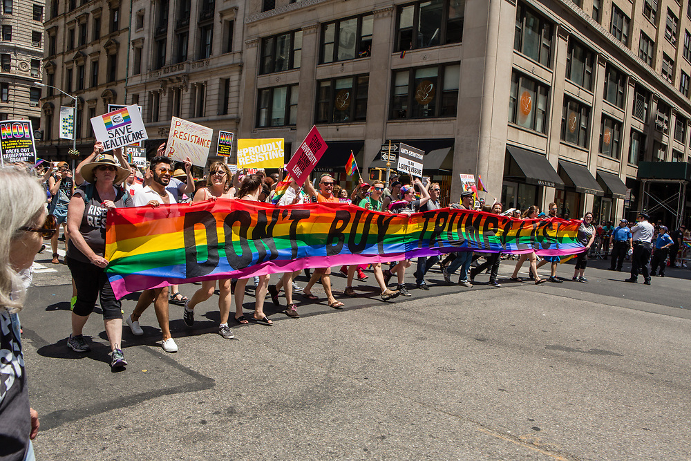 """New York, NY - 25 June 2017. New York City Heritage of Pride March filled Fifth Avenue for hours with groups from the LGBT community and it's supporters. A group of marchers from Refuse Fascism with a street-wide banner reading """"Don't buy Trump's lies."""""""