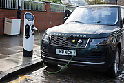Range Rover SUV car at an electric charging point on 27th November 2019 in London, United Kingdom. An electric car is an automobile that is propelled by one or more electric motors, using electrical energy stored in rechargeable batteries or another energy storage device. The resulting drop in harmful emissions makes eco cars an ecologically sound alternative to regular fuel cars.