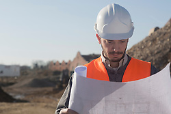 Young male engineer holding blueprint at construction site, Freiburg Im Breisgau, Baden-Wuerttemberg, Germany