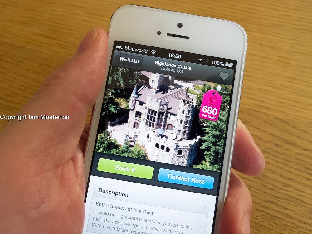 detail of iPhone 5 with Airbnb travel accommodation app for booking rooms showing available castle