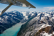 """Aerial view of Rendu Glacier & Rendu Inlet, in West Arm of Glacier Bay National Park, Alaska, USA. Flightseeing from Skagway or Haines is a spectacular way to see Glacier Bay. We were bedazzled by Mountain Flying Service's 1.3-hour West Arm tour from Skagway. Glacier Bay is honored by UNESCO as part of a huge Biosphere Reserve and World Heritage site shared between Canada and the United States. In 1750-80, Glacier Bay was totally covered by ice, which has since radically melted away. In 1794, Captain George Vancover found Icy Strait on the Gulf of Alaska choked with ice, and all but a 3-mile indentation of Glacier Bay was filled by a huge tongue of the Grand Pacific Glacier, 4000 feet deep and 20 miles wide. By 1879, naturalist John Muir reported that the ice had retreated 48 miles up the bay. In 1890, """"Glacier Bay"""" was named by Captain Beardslee of the U.S. Navy. Over the last 200 years, melting glaciers have exposed 65 miles of ocean. As of 2019, glaciers cover only 27% of the Park area. Since the mid 1900s, Alaska has warmed 3 degrees Fahrenheit and its winters have warmed nearly 6 degrees. Human-caused climate change induced by emissions of greenhouse gases continues to accelerate warming at an unprecedented rate. Climate change is having disproportionate effects in the Arctic, which is heating up twice as fast as the rest of Earth."""