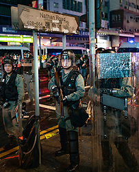 Hong Kong, China. 13th October 2019. Woman suspected of being pro-Beijing is assaulted by pro-democracy protestors in Mongkok district in Kowloon on Sunday evening. This incident was one of several throughout Hong Kong on Sunday which saw acts of vandalism carried out by a minority in the pro-democracy movement. Riot police on Nathan Road in Mongkok. Iain Masterton/Alamy Live News.