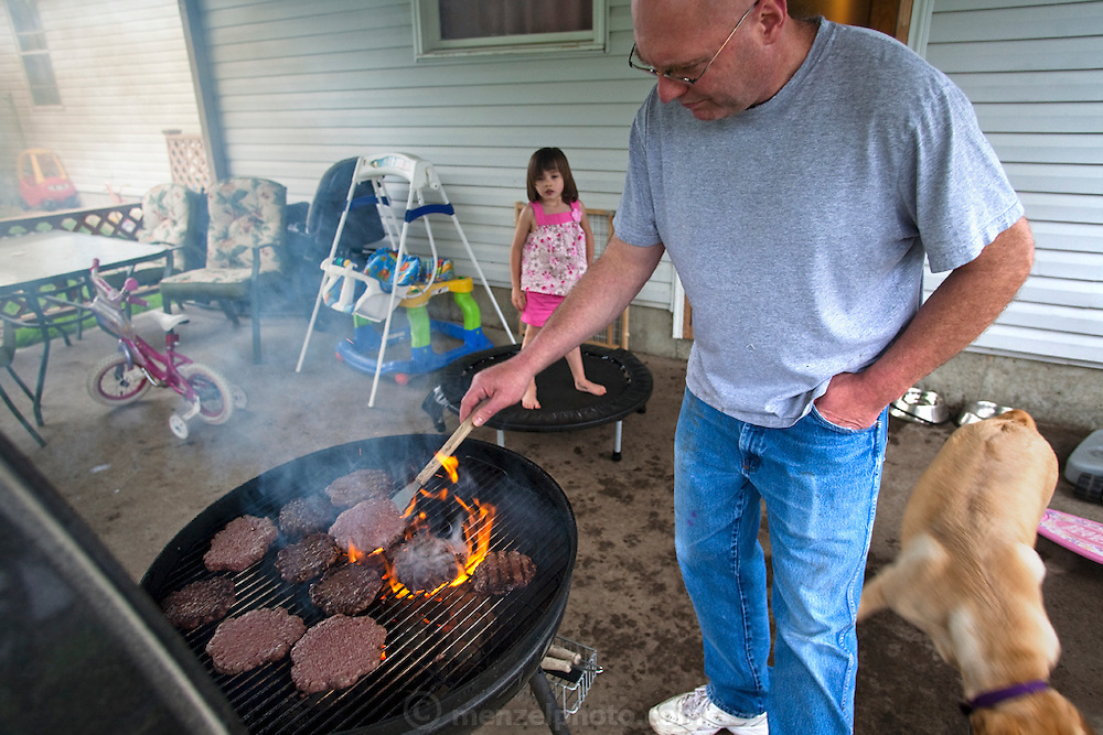 At home after work, meat grinder Kelvin Lester grills hamburger patties, well-done, for the family's supper as his adopted daughter Kiara looks on. (From the book What I Eat: Around the World in 80 Diets.) The caloric value of his typical day's worth of food in June was 2,600 kcals. He is 44; 5 feet 11 inches and 195 pounds.
