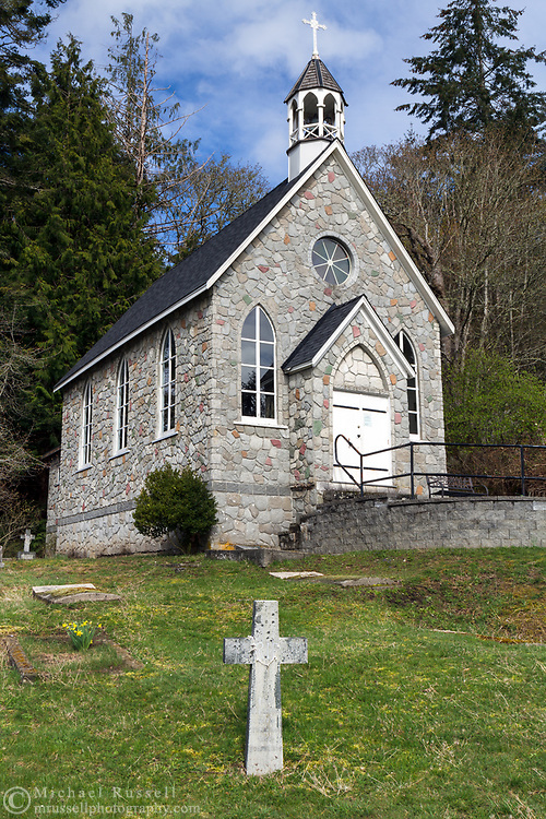 The historic St. Paul's Church at Fulford Harbour on Salt Spring Island, British Columbia, Canada.  The church was founded in 1878 and built between 1880 and 1885.  The cross in the foreground is part of the church cemetery and marks the resting place of Alan Blackburn (1865-1925).