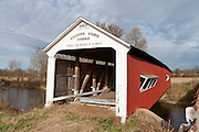 """Thorpe Ford Covered Bridge (163 feet long) was built in Burr Arch style over Big Raccoon Creek in 1912 by J.A. Britton on Catlin Road in Parke County, Indiana, USA. Red and white paint protects the wood. The traditional """"Cross this bridge at a walk"""" sign required slow vehicle speed, but traffic is now diverted to an adjacent modern bridge."""