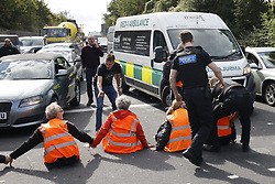 © Licensed to London News Pictures. 29/09/2021. Swanley, UK. Motorist and police drag away an activist from the Insulate Britain climate change protest group  to allow an ambulance through as they block the road near to junction 3 of the M25 motorway near Swanley for the second time today. 11 members of the campaign group were detained at the same junction earlier today. This is the seventh time in just over two weeks that activists have disrupted traffic on London's orbital motorway despite the government being granted a temporary High Court Injucntion banning the group from protesting on the M25. 50 protesters who were detained after Monday's protest, on junction 14 of the M25 at Heathrow, were released. Photo credit: Peter Macdiarmid/LNP