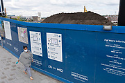 Woman wearing a face mask passes the construction site hoardings for the HS2 mainline station at Curzon Street on 3rd August 2020 in Birmingham, England, United Kingdom. The Curzon Street Masterplan covers a 141 hectare area of regeneration, focussed on HS2 Curzon Street station in Birmingham city centre, combined with approximately 700 million in investment into the surrounding area including new homes and commercial developments. High Speed 2 is a partly planned high speed railway in the United Kingdom with its first phase in the early stages of construction, the second phase is yet to receive full approval and the third is subject to merging with Northern Powerhouse Rail, a separate project.