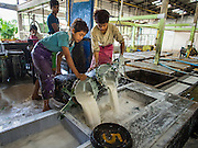 """16 DECEMBER 2014 - CHUM SAENG, RAYONG, THAILAND: Workers pour barrels of liquid latex into the intake at a large rubber plantation near Chum Saeng, Thailand. The latex will be made into smoked rubber sheets. Thailand is the second leading rubber exporter in the world. In the last two years, the price paid to rubber farmers has plunged from approximately 190 Baht per kilo (about $6.10 US) to 45 Baht per kilo (about $1.20 US). It costs about 65 Baht per kilo to produce rubber ($2.05 US). Prices have plunged 5 percent since September, when rubber was about 52Baht per kilo. Some rubber farmers have taken jobs in the construction trade or in Bangkok to provide for their families during the slump. The Thai government recently announced a """"Rubber Fund"""" to assist small farm owners but said prices won't rebound until production is cut and world demand for rubber picks up.    PHOTO BY JACK KURTZ"""