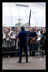1st Sept, 2005. Mass evacuation of New Orleans begins. A Louisiana State Trooper holds his shotgun in the air as authorities attempt to hold back thousands of refugees on the berge of chaos awaiting busses out of New Orleans.