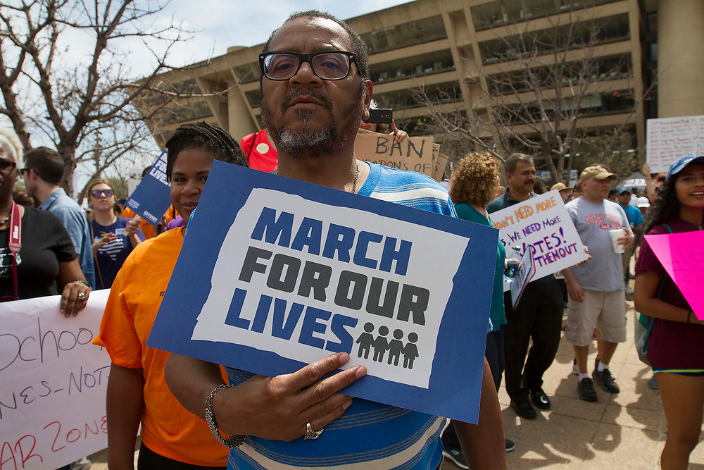 A parent stands in silence in front of Dallas City Hall in downtown Dallas during the March for Our Lives, to protest the ongoing lack of security at schools across the country after the latest spate of shootings.