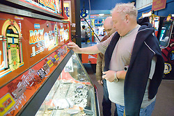 Men playing the slot machines in the amusement arcade on a day trip to Skegness organised by the Nottingham Disabled Friendship club,
