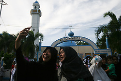 September 12, 2016 - Philippines - Young ladies take a selfie in front of the Blue Mosque after the morning prayers. Filipino-Muslims celebrated Eid Al-Adha early Monday morning with prayers and games at the Blue Mosque in Taguig, Metro Manila. (Credit Image: © J Gerard Seguia via ZUMA Wire)