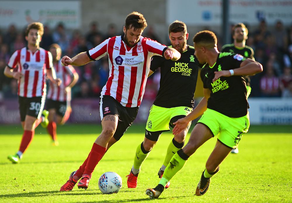 Lincoln City's Ollie Palmer vies for possession with Cambridge United's Gary Deegan and Jake Carroll<br /> <br /> Photographer Andrew Vaughan/CameraSport<br /> <br /> The EFL Sky Bet League Two - Lincoln City v Cambridge United - Saturday 14th October 2017 - Sincil Bank - Lincoln<br /> <br /> World Copyright © 2017 CameraSport. All rights reserved. 43 Linden Ave. Countesthorpe. Leicester. England. LE8 5PG - Tel: +44 (0) 116 277 4147 - admin@camerasport.com - www.camerasport.com