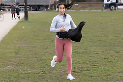 © Licensed to London News Pictures. 11/03/2021. London, UK. A woman jogs on a windy Blackheath Common in South East London. A yellow weather warning for wind is in place in parts of the UK. Photo credit: George Cracknell Wright/LNP