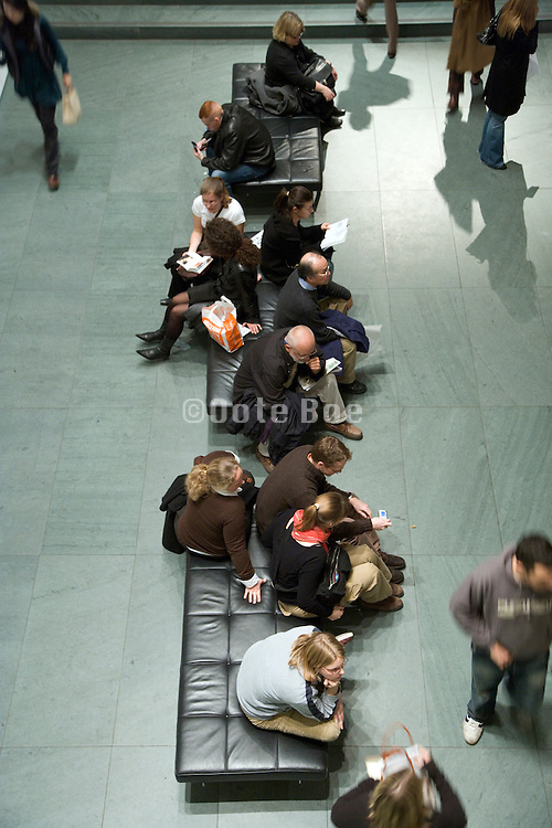 groups of people sitting and chatting in the lobby of a public space