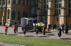 The Duke of Edinburgh's coffin, covered with his Personal Standard, is carried on the purpose built Land Rover Defender, followed by the Prince of Wales and Princess Anne, and watched by members of the Royal family from the Galilee Porch of St George's Chapel, Windsor Castle, Berkshire, during the funeral of the Duke of Edinburgh. Picture date: Saturday April 17, 2021.