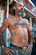 Beirut, Lebanon - September 18, 2010: A Lebanese man stands outside a shop in the Shatila neighborhood of Beirut, numerous tattoos on his body. The man is a Shia Muslim, and his tattoos include family members and Woody Woodpecker.