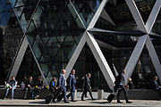 Business people walk beneath the architectural struts of the Swiss Re at 30 St. Mary Axe in the City of London, the capitals financial district also known as the Square Mile, on 6th April 2017, in London, England.