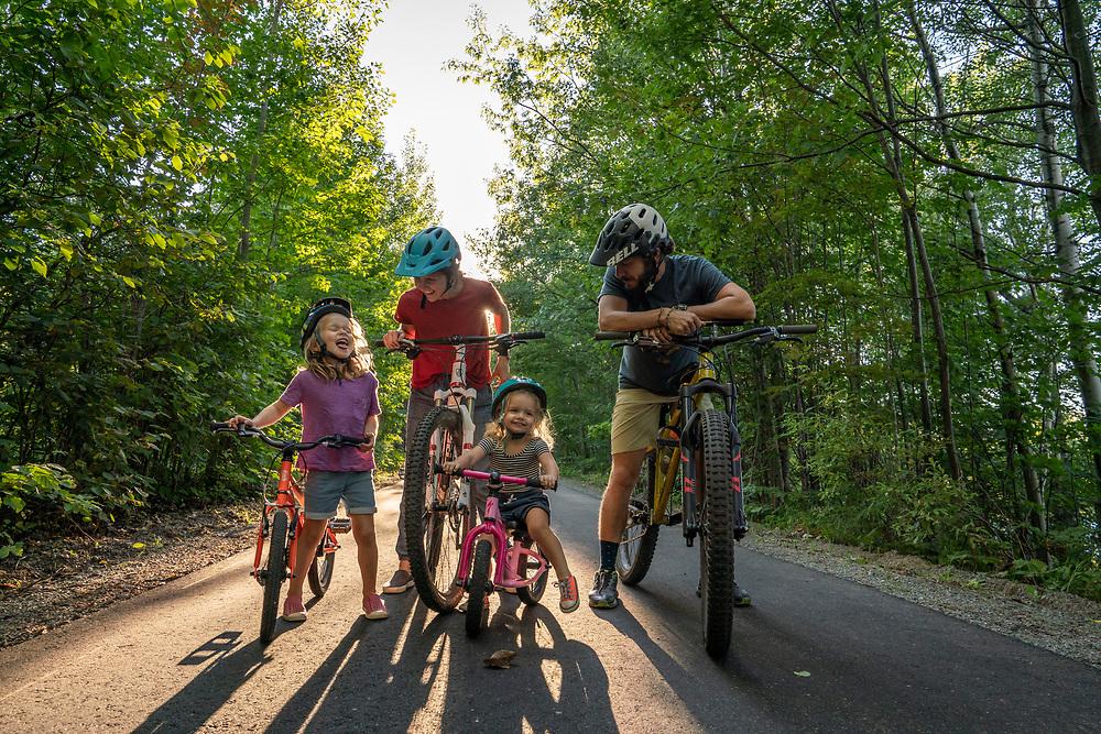 Multigenerational family bike ride along the Iron Ore Heritage Trail in Marquette, Michigan.