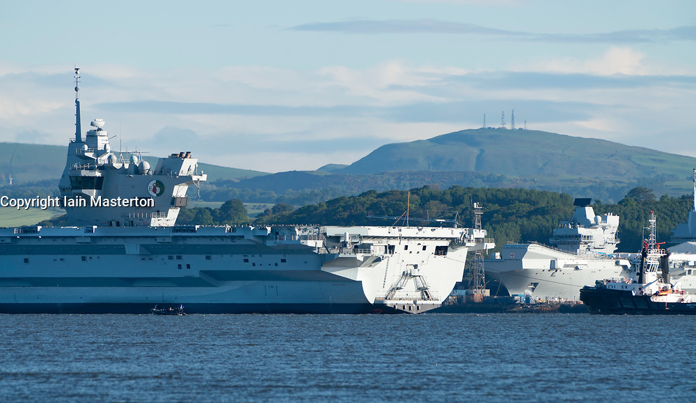 Rosyth ,Scotland, UK. 22 May 2019. Aircraft carrier HMS Queen Elizabeth moored off Rosyth in the River Forth after leaving dry dock yesterday after a visit to her home port. She will leave the Forth today and return to sea in preparation for Westlant 19 deployment which is designed to focus on the operations of her F-35 fighter aircraft. Pictured; Rare view of both of the Royal Navy's aircraft carriers. HMS Queen Elizabeth on left and HMS Prince of Wales still under construction in shipyard at Rosyth.