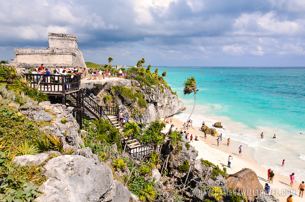 The ruins of the Maya civilization city at Tulum, on the coast of Mexico's Yucatan Peninsula. At top left is the stone structure known as El Castillo. In the center is a walkway from the ruins down to the white sandy beach below.