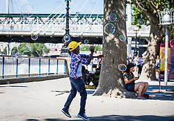 © Licensed to London News Pictures. 19/07/2016. London, UK. Children chase after bubbles on London's Southbank. Temperatures in the capital soared to 32 degrees celsius, the hottest day of the year so far. Photo credit: Rob Pinney/LNP