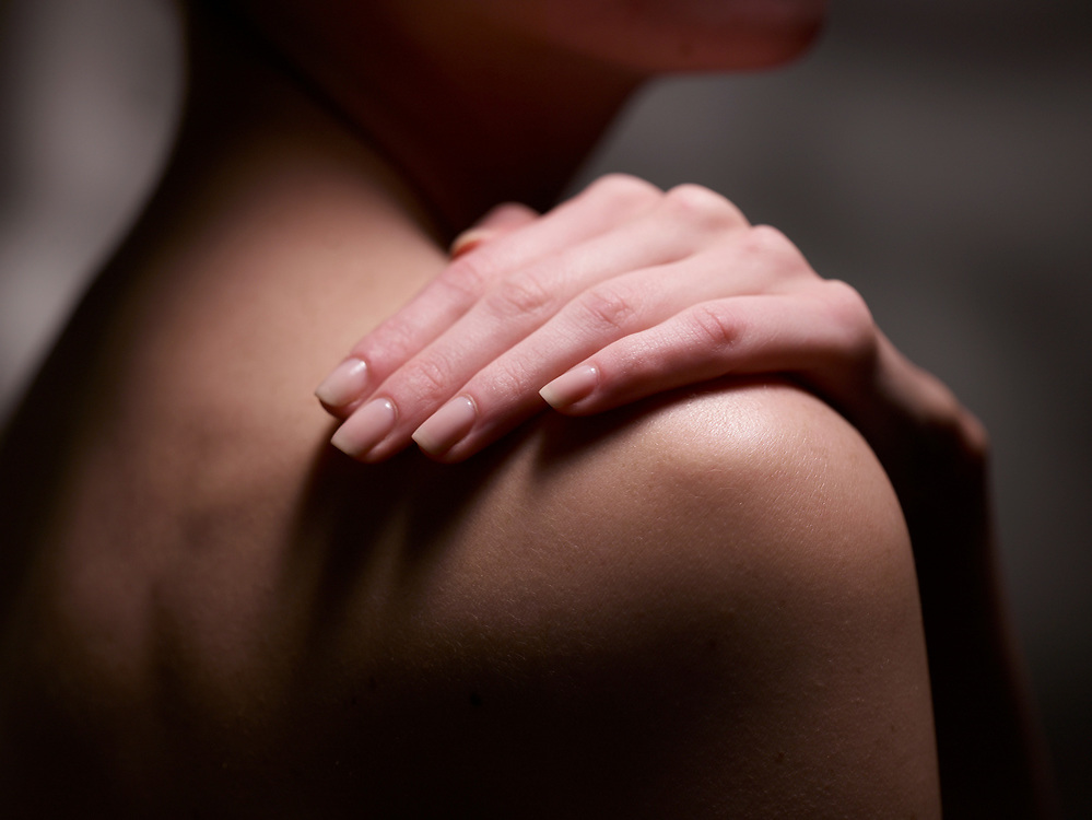 Dramatic light on woman's hand caressing her shoulder