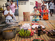"""07 AUGUST 2014 - BANGKOK, THAILAND: People pray in front of food left for the poor at Pek Leng Keng Mangkorn Khiew Shrine. Thousands of people lined up for food distribution at the Pek Leng Keng Mangkorn Khiew Shrine in the Khlong Toei section of Bangkok Thursday. Khlong Toei is one of the poorest sections of Bangkok. The seventh month of the Chinese Lunar calendar is called """"Ghost Month"""" during which ghosts and spirits, including those of the deceased ancestors, come out from the lower realm. It is common for Chinese people to make merit during the month by burning """"hell money"""" and presenting food to the ghosts. At Chinese temples in Thailand, it is also customary to give food to the poorer people in the community.     PHOTO BY JACK KURTZ"""