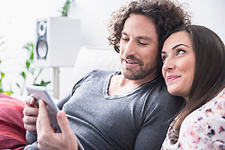Couple using a digital tablet at home, Munich, Bavaria, Germany