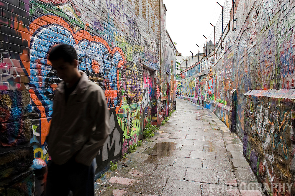 "A pedestrian walks down ""Graffiti Alley""  in Ghent, Belgium, on Friday, Sept. 12, 2008. The street, which is actually named Werregaran Straat, was made a safe zone for ""taggers"" to ply their art in an attempt to deter graffiti artists from vandalizing the city. (Photo © Jock Fistick)"