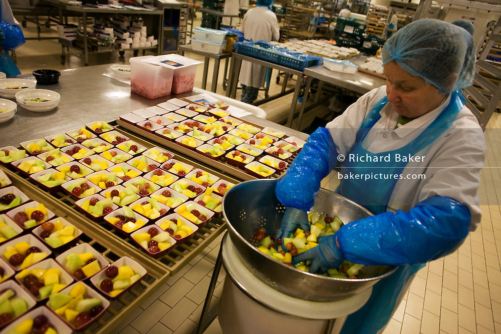 A female employee prepares fruit salads destined for airline meals by Gate Gourmet at Heathrow Airport. .