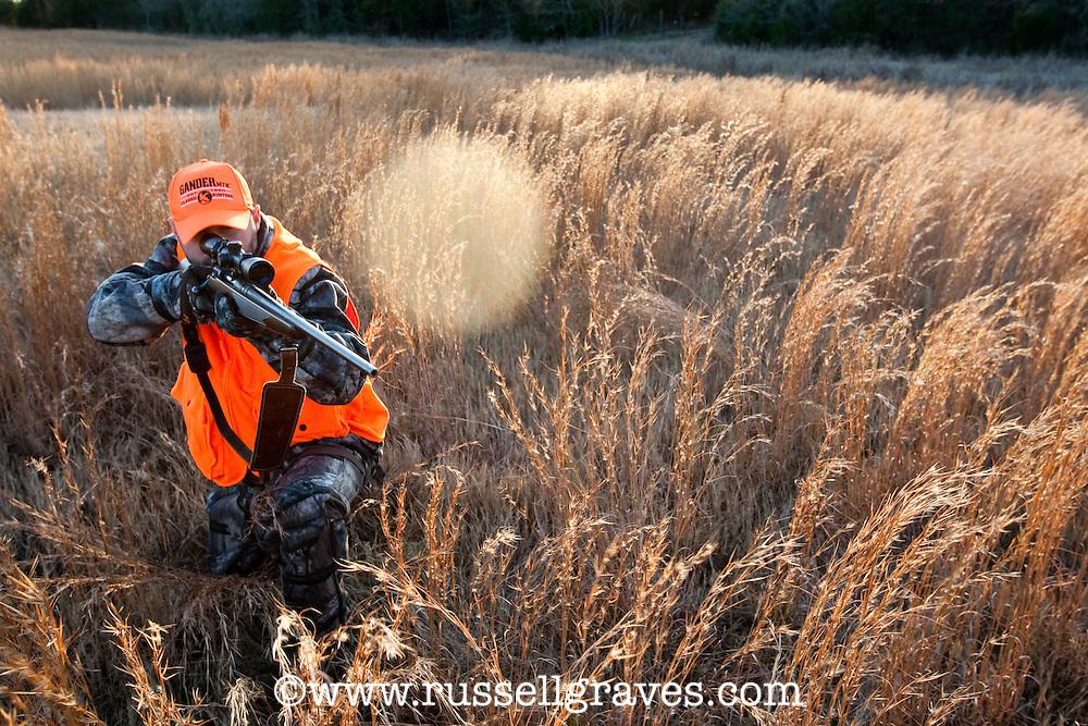 BACKLIT DEER HUNTER WEARING BLAZE ORANGE IN A GRASS MEADOW