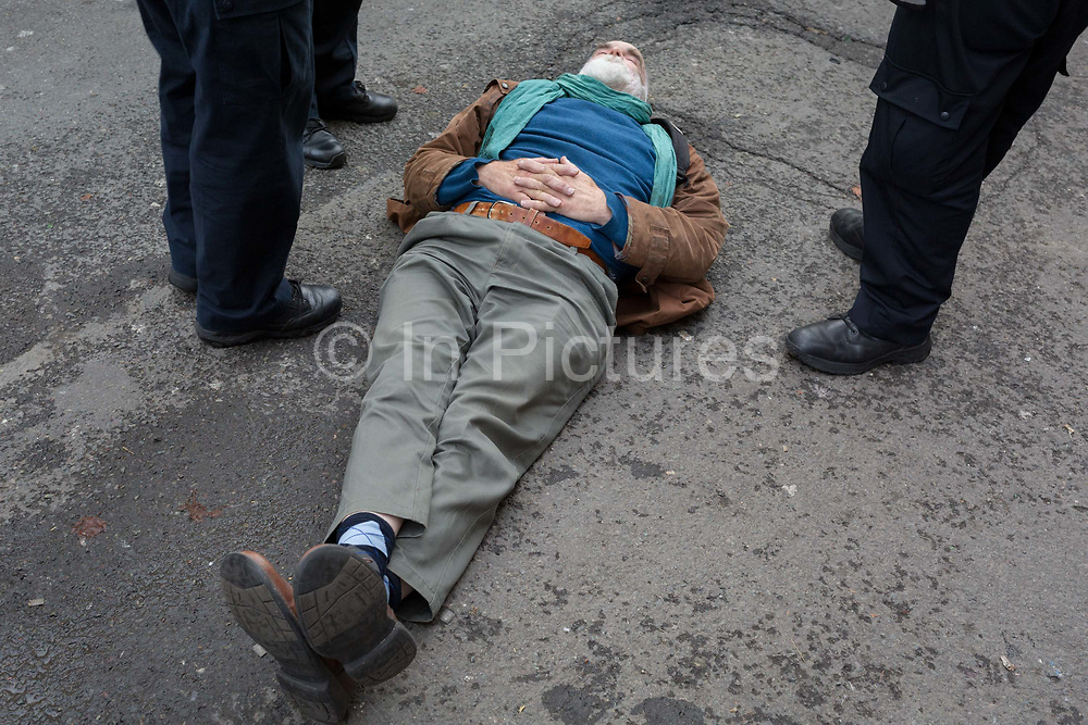 An environmental activist is lies on the ground after being arrested while protesting about Climate Change during the blockade of Whitehall in central London, part of a two-week prolonged worldwide protest by members of Extinction Rebellion, on 16th October 2019, in Westminster, London, England.