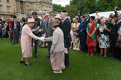 Queen Elizabeth II (left) greets guests during a garden party at Buckingham Palace in London.
