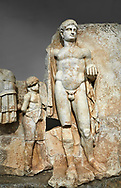 Close up of a Roman Sebasteion relief  sculpture of Emperor Nero with captive, Aphrodisias Museum, Aphrodisias, Turkey.  Against a grey background.<br /> <br /> Naked warrior emperor Nero holds the orb of world rule in one hand and crowns the military trophy with the other. Between the trophy and the emperor stands a bound captive boy. He wears long barbarian trousers and looks up at Nero. .<br /> <br /> If you prefer to buy from our ALAMY STOCK LIBRARY page at https://www.alamy.com/portfolio/paul-williams-funkystock/greco-roman-sculptures.html . Type -    Aphrodisias     - into LOWER SEARCH WITHIN GALLERY box - Refine search by adding a subject, place, background colour, museum etc.<br /> <br /> Visit our ROMAN WORLD PHOTO COLLECTIONS for more photos to download or buy as wall art prints https://funkystock.photoshelter.com/gallery-collection/The-Romans-Art-Artefacts-Antiquities-Historic-Sites-Pictures-Images/C0000r2uLJJo9_s0