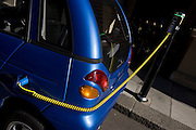 A power cable plugs into the place of a petrol cap while recharging G-Wiz car in central London. A power cable plugs into the place of a petrol cap while recharging a G-Wiz AEV (Automatic Electric Vehicle) car. The car is parked at the kerbside in Dover Street and is hooked up to a recharging point. The AEV has a range of up to 48 miles per charge with a certified top speed of 50 mph. A charging station, also called an electric recharging point and EVSE (Electric Vehicle Supply Equipment) supplies electricity for the recharging of electric vehicles (including plug-in hybrids). Although most electric cars can be recharged from a domestic wall socket, many support faster charging at higher voltages and currents that require dedicated equipment with a specialized connector..