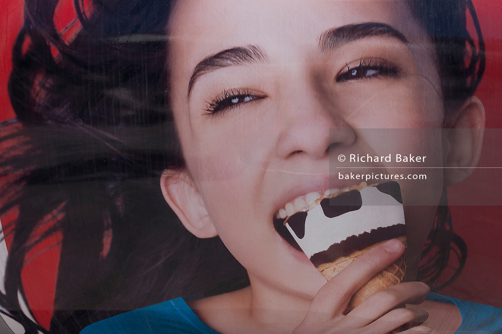 A detail of an advert - a picture of a girl enjoying an ice cream cone with chocolate chips seemingly the shape of bad teeth, on 12th July 2016, at Estoril, near Lisbon, Portugal. Estoril is a town and a former civil parish in the municipality of Cascais, Portugal, on the Portuguese Riviera. (Photo by Richard Baker / In Pictures via Getty Images)