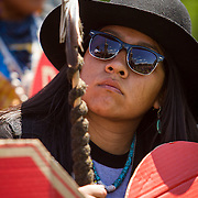 """Carrie Sage Curley, San Carlos Apache, watches Wendsler Nosie, Sr, tribal councilman, speak to fellow members of the San Carlos Apache Tribe and their supporters in front of the United States Capitol to protest the transfer of Apache land to a private Australian-British mining corporation.  In December 2014, a rider to the National Defense Authorization Act handed over Oak Flat to a foreign-owned company looking to mine copper.  The Apache are currently """"occupying"""" Oak Flat, and travelled to D.C. to protest the action.  In response, Rep. Raul Grijalva (D-AZ-3), proposed the Save Oak Flat Act (H.R. 2811) in June, 2015 to repeal the land exchange.  John Boal Photography"""