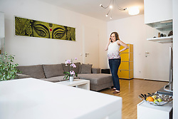 Pregnant woman standing in living room and talking on mobile phone, Munich, Bavaria, Germany