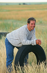 handome man leaning on an old tire on a ranch