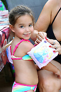 Smiling young girl of 4 with inflatable armbands ready to enter a swimming pool